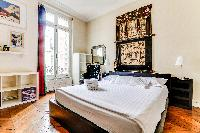 second bedroom features a king-sized style bed and ensuite in a 4-bedroom Paris luxury apartment