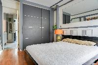 master bedroom with a queen size bed and en suite bathroom in a 2-bedroom Paris luxury apartment