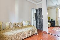 second bedroom with a single bed, mirror and en suite bathroom in a Paris luxury apartment