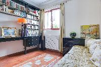 neatly-stocked, bright, and comfortable bedroom in a 2-bedroom Paris luxury apartment