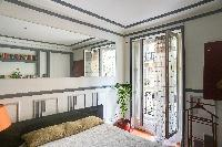 a large window that leads to a small balcony with street view in a  2-bedroom Paris luxury apartment