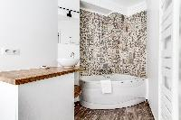 an en suite bathroom with sink, handheld shower and a gorgeous bathtub in a 3-bedroom Paris luxury a