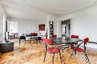 spacious dining area with 4 seats in a 3-bedroom Paris luxury apartment