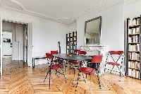 spacious dining area with 4 seats, mirror, ornamental fireplace and book shelves in a 3-bedroom Pari