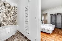 master bedroom and en suite bathroom with artistic walls  in a 3-bedroom Paris luxury apartment