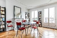 spacious dining area with 4 seats, bright windows and book shelves in a 3-bedroom Paris luxury apart