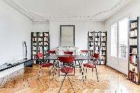 spacious dining area with 4 seats and book shelves in a 3-bedroom Paris luxury apartment