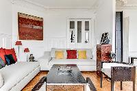 sitting area with comfortable sofas and armchairs in a 3-bedroom Paris luxury apartment