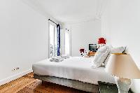 bedroom with queen size bed, TV, and studydesk and chair in a 3-bedroom Paris luxury apartment