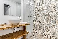 A separate modern bathroom with sink and shower in a 3-bedroom Paris luxury apartment
