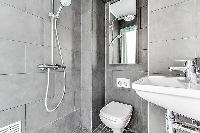 a slate grey and white full bathroom with both handheld and rain shower, toilet and sink in a charmi