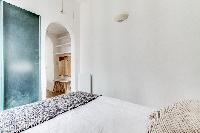 contemporary bedroom and a full bathroom in a charming studio Paris apartment