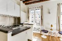 functional kitchenette and dining area with a table and two modern chairs in a studio Paris luxury a