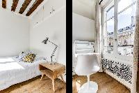 comfortable double bed and bright windows in a studio Paris luxury apartment