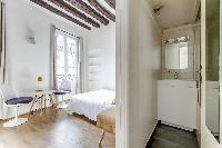 modern sleeping area, dining area, and bathroom in a studio Paris luxury apartment
