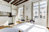 sleeping area with a comfortable queen size bed in a studio Paris luxury apartment