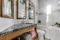 spotless modern tile and marble finished bathroom with shower, bathtub, sink, toilet, and a hairdrye