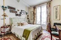 charming bedroom with a double size bed with the finest linens and a desk in a 1-bedroom Paris luxur