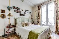 charming bedroom with a large glass window which allows natural light to pass through  in a 1-bedroo