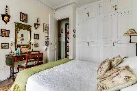charming bedroom with ample of storage spaces and lovely decors in a 1-bedroom Paris luxury apartmen