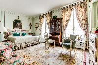 elegant bedroom fitted with queen size bed, desk and chair, arm chair, and tall French windows in 3-