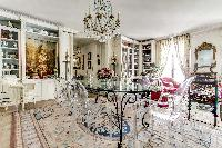 elegant dining area with a modern glass dining table and chairs for 6 in 3-bedroom Paris luxury apar