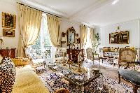 elegant living room with comfortable sofas, elegant arm chairs, working desk, modern center piece, l