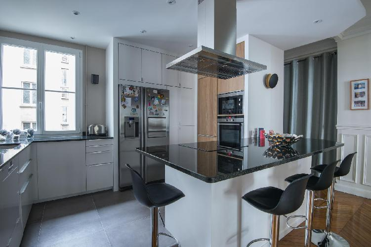 sleek black-and-white kitchen and breakfast bar with stools in Paris luxury apartment