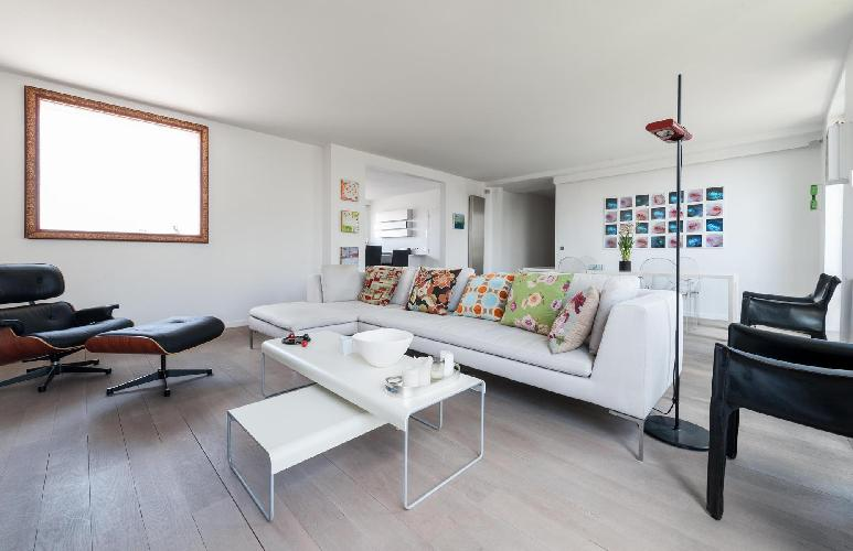 open-plan living and dining area furnished with a fresh white sofa striped with printed cushions, a