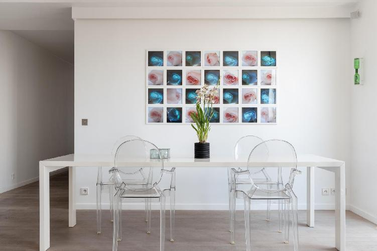 gleaming dining table lined with Perspex ghost chairs, zinc cupboards punched with tree silhouettes