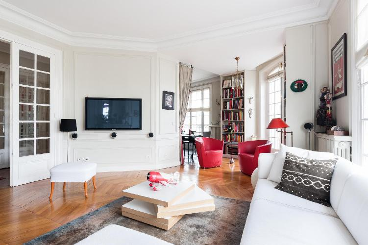 elegant living area designed with antiques, rouge tub chairs, art books, and bold paintings in Paris