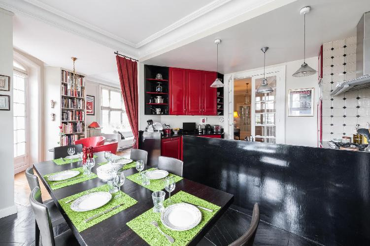 well-equipped scarlet kitchen and dining area with long dining table for 6 in Paris luxury apartment