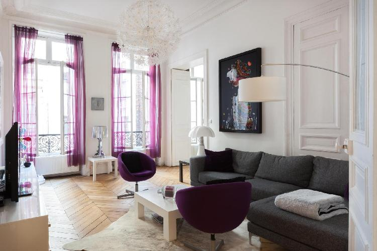 living area with interiors designed with bold strokes, purple accents and sleek furniture contrastin