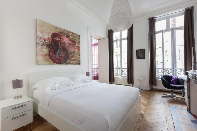 artfully decorated bedroom with queen size bed in Paris luxury apartment