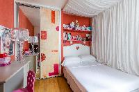 pretty single bedroom with a princess-style bed and bright-strawberry bookshelves in Paris luxury ap