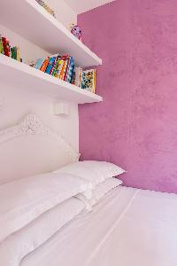 pretty lavender-walled double bed and bookshelves in Paris luxury apartment