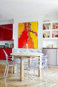 round wooden dining table with 4 ghost chairs, dramatic orange canvas, and bookshelves in Paris luxu