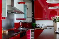 vibrant red kitchen with sleek breakfast bar and red ceiling lamps in Paris luxury apartment