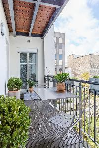 serene terrace with potted plants, table for 3 overlooking the courtyard in Paris luxury apartment