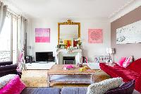 vibrant living area with abstract artworks, rose-pink paintings, velvet chaise longue, and tall drap