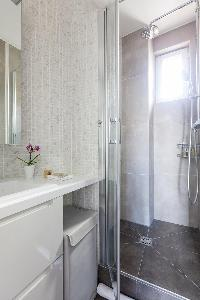 sleek shower area in gray tiles in Paris luxury apartment