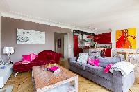 vibrant living area with abstract artworks, dramatic orange canvas, and red kitchen in Paris luxury