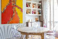round wooden dining table with 4 ghost chairs, dramatic orange canvas, bookshelves, and tall draped