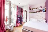 pretty pink and lavender bedroom with bright pink draped window, toys, and books for kids in Paris l