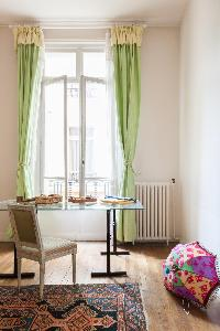 cozy bedroom with glass study desk facing a fine set of spring-green curtains in Paris luxury apartm