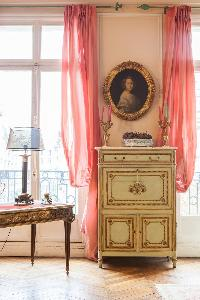 antique cabinet drawer beneath a portrait between salmon pink drape dressed the tall windows in Pari