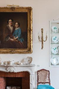 fireplace beneath antique portrait in Paris luxury apartment