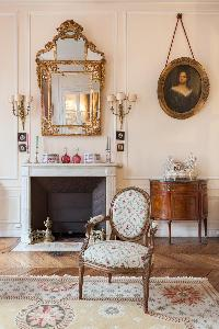a classic 3-bedroom Paris luxury apartment with historic portraits and gilded frames share space wit