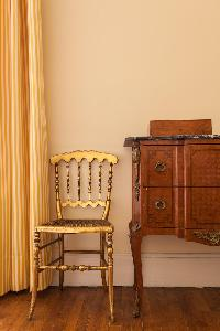 golden steel chair, antique cabinet drawer, and yellow striped drape in Paris luxury apartment