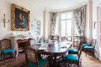 classic dining area with a large formal dining room furnished with cane-backed chairs upholstered in